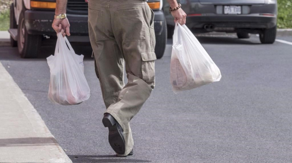 A shopper leaves a grocery store carrying his groceries in plastic bags in Brossard, Que. on August 30, 2016.
