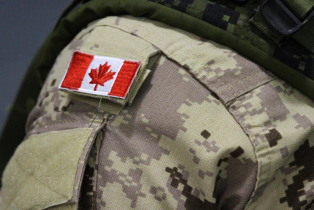 A Canadian flag sits on a member of the Canadian forces who are leaving from CFB Trenton, in Trenton, Ont., on Thursday, Oct. 16, 2014.