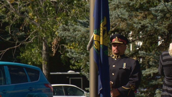 Chief Davis lowers the flag on his last day of service in the Lethbridge community.