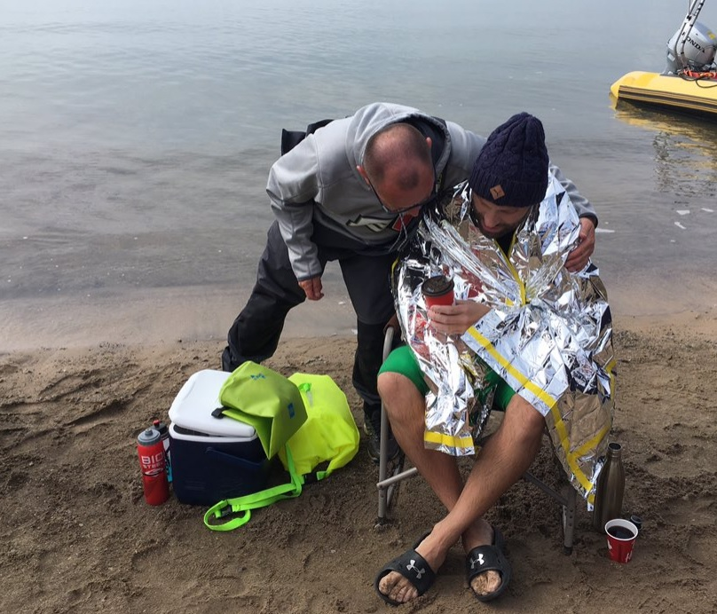 Daniel Zin warms up after completing his swim across Lake Erie.