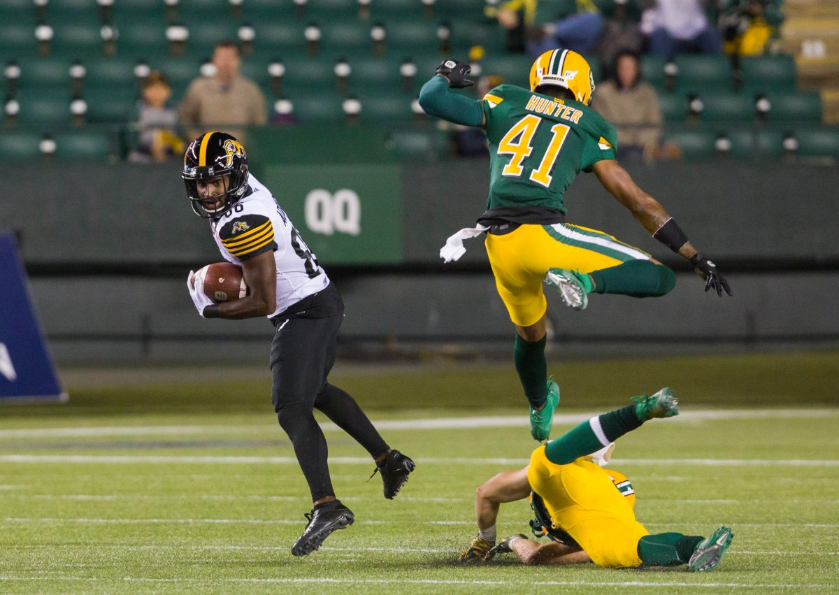 Hamilton Tiger-Cats wide receiver Bralon Addison (86) dodges tackles by Edmonton Eskimos defensive back Monshadrik Hunter (41) and safety Jordan Hoover (28) to run in a touchdown during first half CFL action in Edmonton, Alta., on Friday September 20, 2019.