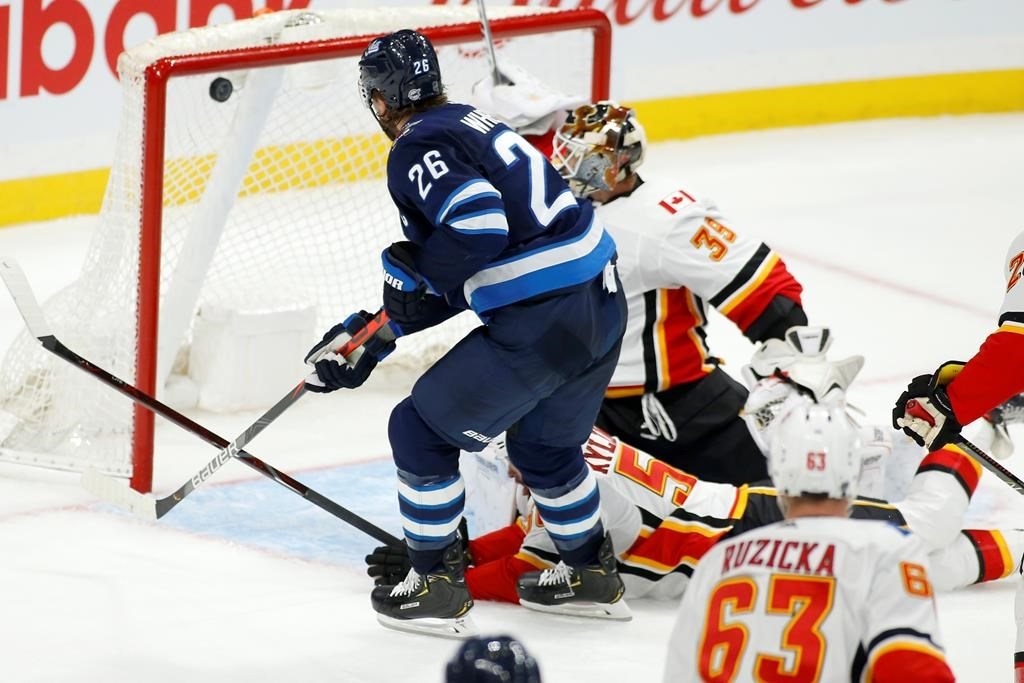 Winnipeg Jets' Blake Wheeler (26) scores on Calgary Flames goaltender Cam Talbot (39) during third period NHL pre-season action in Winnipeg on Sunday, Sept. 22, 2019. THE CANADIAN PRESS/Fred Greenslade.