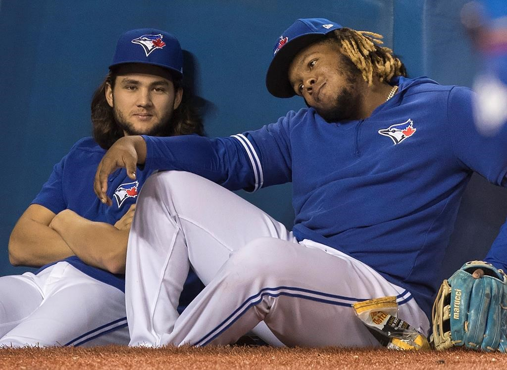 Toronto Blue Jays Vladimir Guerrero Jr. (right) and Bo Bichette sit this one out at edge of dugout in eighth inning of their baseball game against the Tampa Bay Rays in on Sept. 28, 2019.