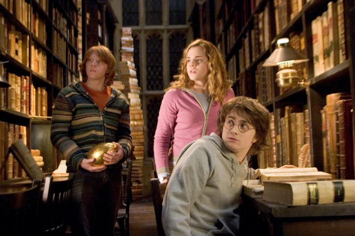 """In this photo provided by Warner Bros., Ron Weasley (Rupert Grint),  Hermione Granger (Emma Watson) and  Harry Potter (Daniel Radcliffe) tries to  find out about the mysterious event that's supposed to take place at Hogwarts  in  """"Harry Potter and the Goblet of Fire.""""  (AP Photo/Warner Bros./Murray Close)."""