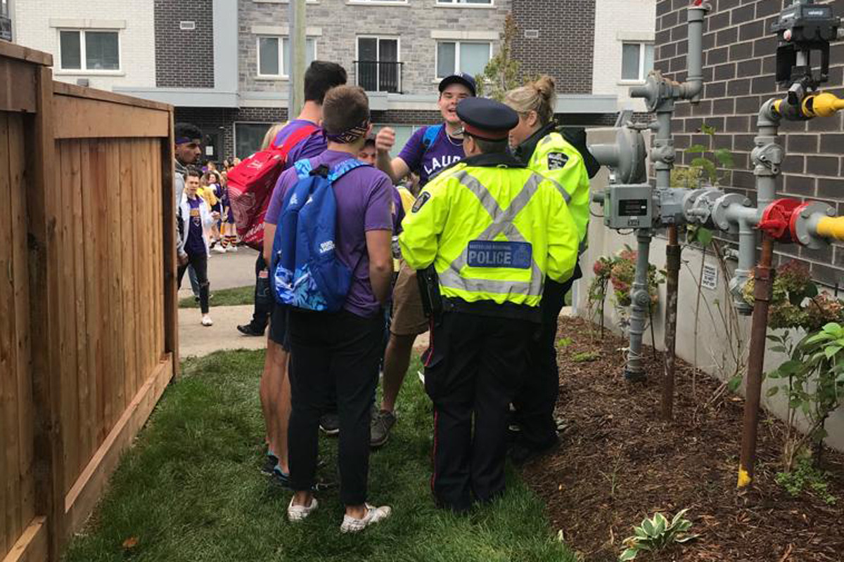 Waterloo Regional Police talk to revellers at Laurier's homecoming celebration.
