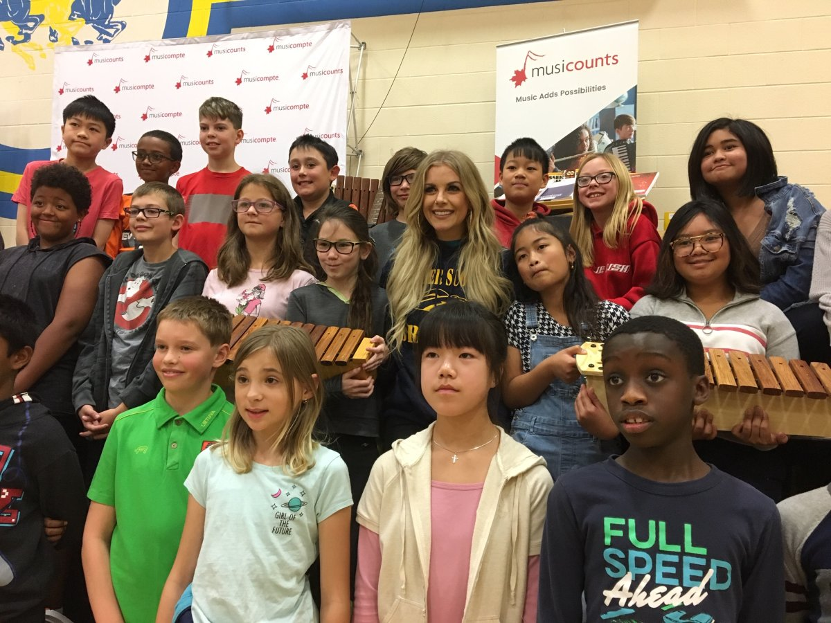 Lindsay Ell poses with students at Calgary's Father Scollen School after presenting the school with a $15,000 grant for musical instruments from the MusiCounts Band Aid program.