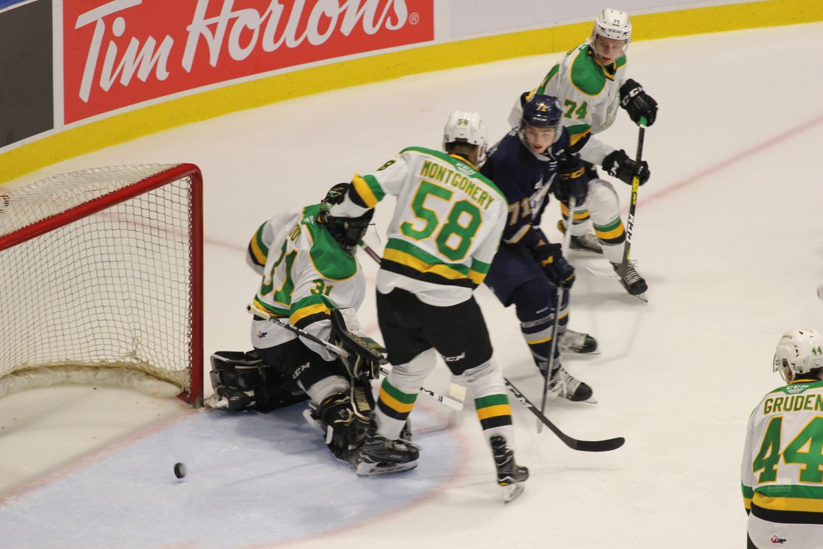 The puck slips through a maze of legs and rolls toward the goal line in a game between the London Knights and the Barrie Colts on Sept. 21, 2019. Barrie won 6-2.
