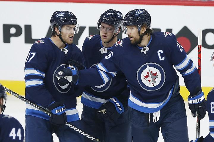Winnipeg Jets' Adam Lowry (17), Andrew Copp (9) and Blake Wheeler (26) celebrate Wheeler's goal against the Minnesota Wild during first period NHL action in Winnipeg on Wednesday, September 18, 2019.