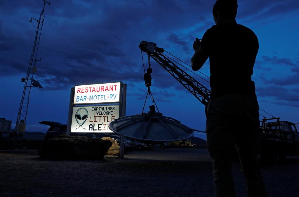 """A man takes a picture of a sign at the Little A'Le'Inn during an event inspired by the """"Storm Area 51"""" internet hoax, Thursday, Sept. 19, 2019, in Rachel, Nev."""