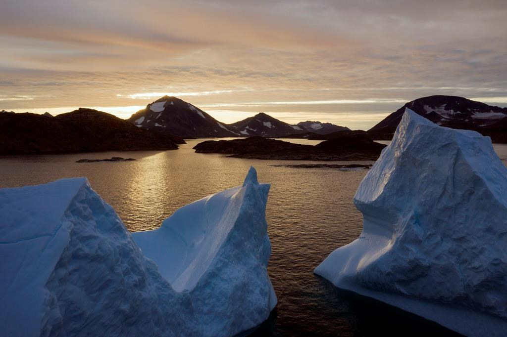 This early Friday, Aug. 16, 2019 file photo shows an aerial view of large Icebergs floating as the sun rises near Kulusuk, Greenland.
