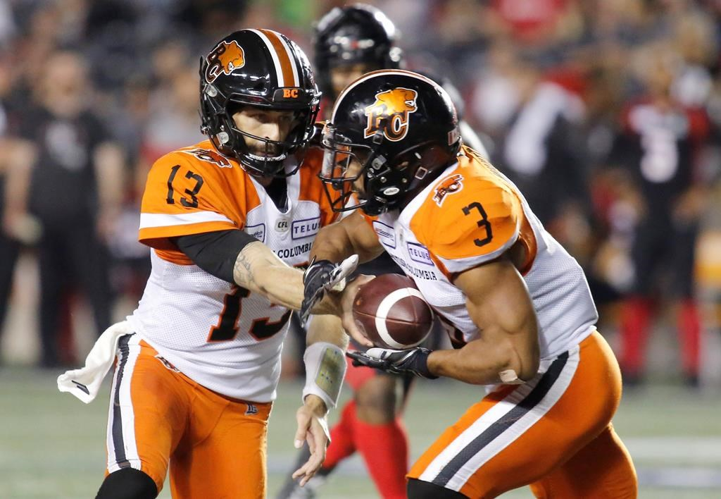 BC Lions quarterback Mike Reilly (13) hands the ball to running back John White IV (3) during second quarter CFL football action against the Ottawa Redblacks in Ottawa on Saturday, September 21, 2019.