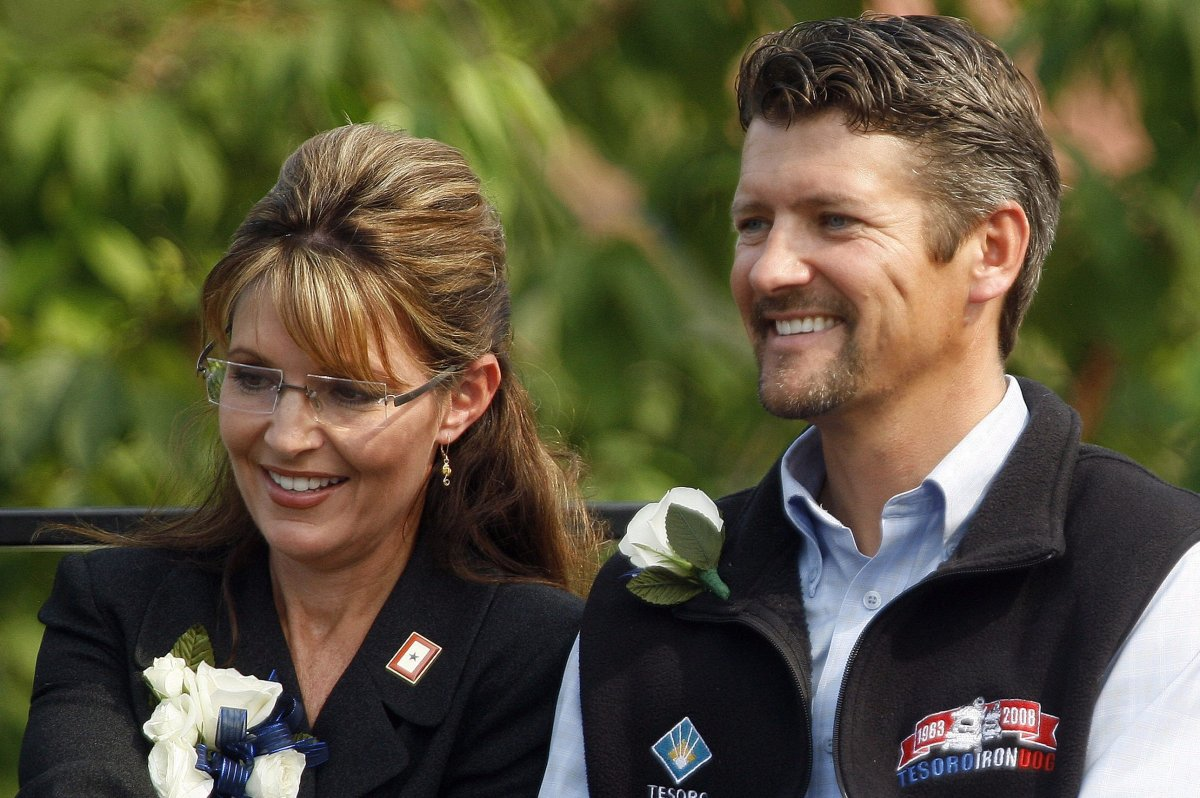 Former Alaska governor Sarah Palin holds her husband Todd's hand as newly sworn-in Gov. Sean Parnell gives his acceptance speech during a ceremony in Fairbanks, Alaska, on July 26, 2009.