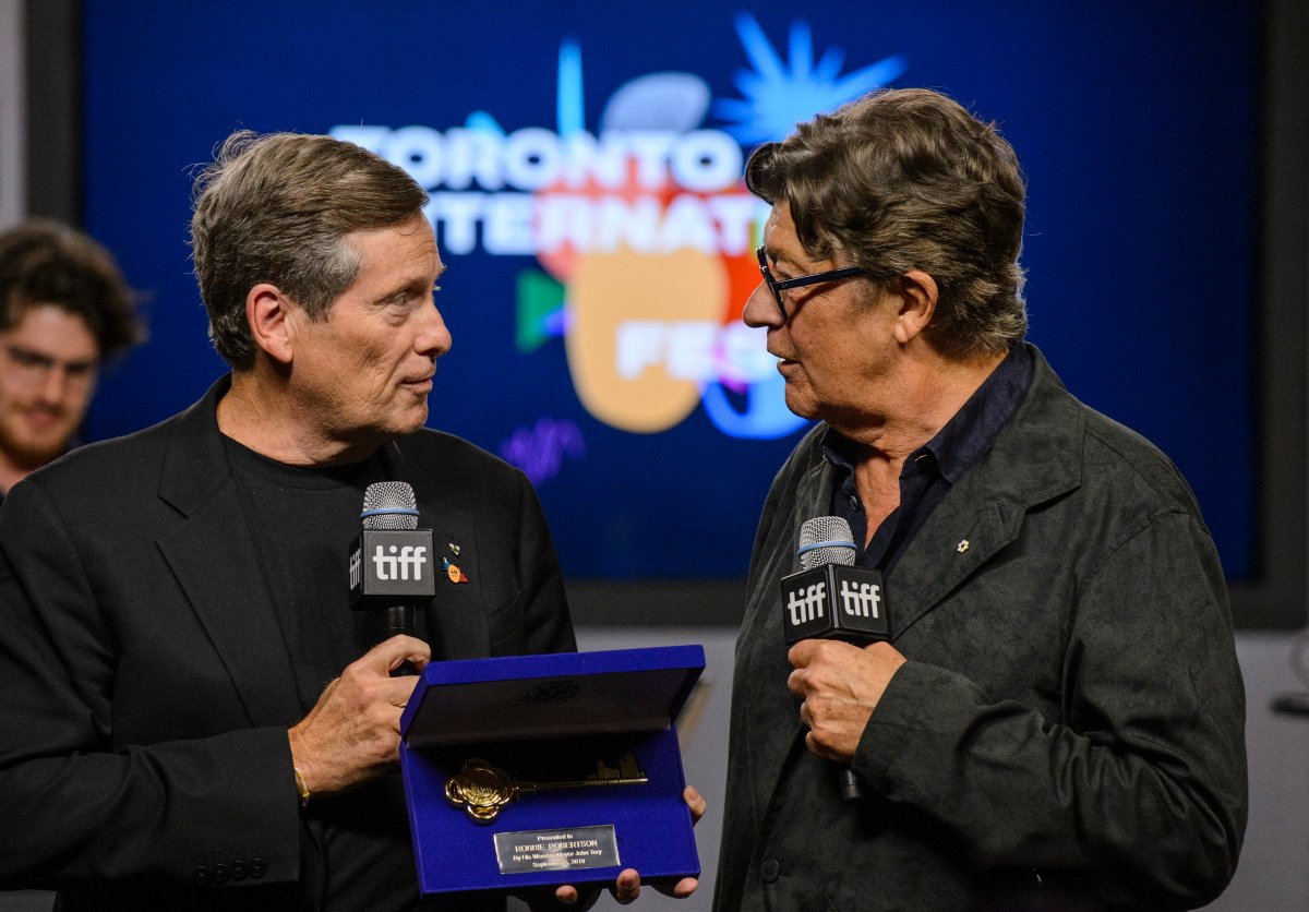 Toronto Mayor John Tory, left, presents Robbie Robertson with a key to the city during a TIFF press conference in Toronto on Thursday.