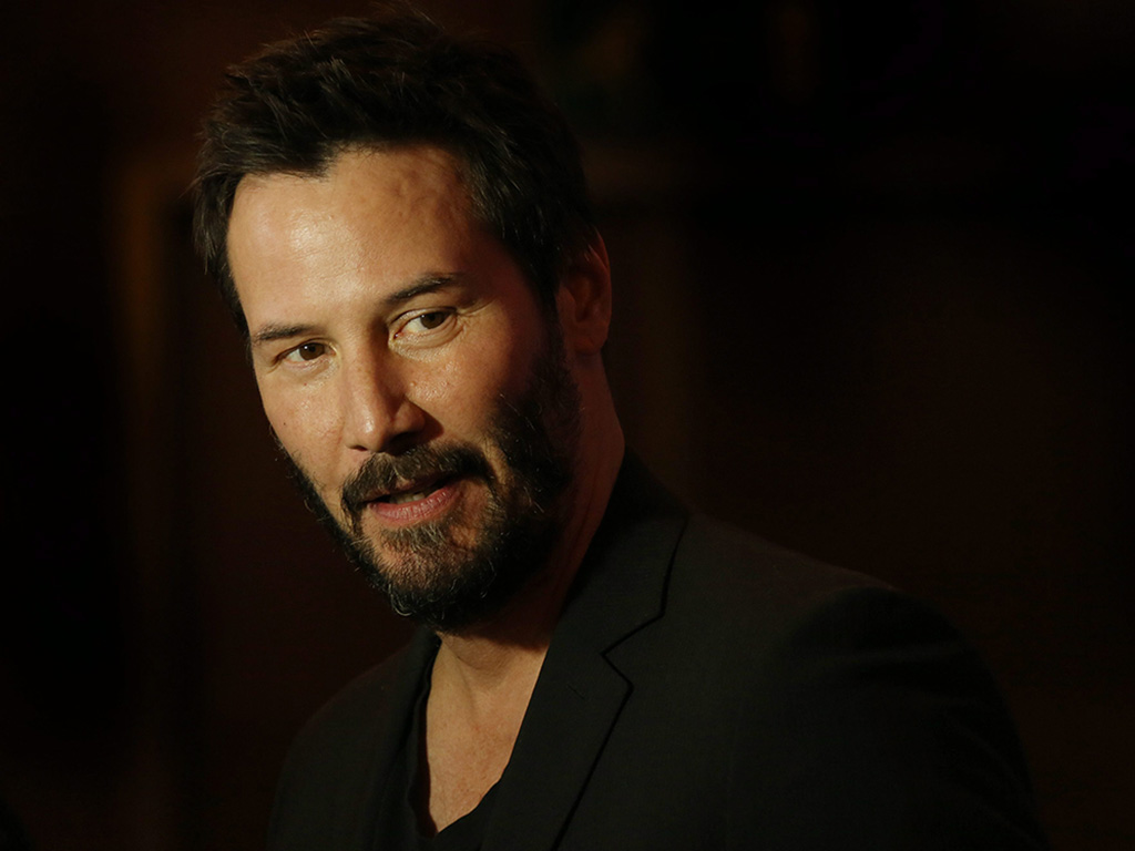 Keanu Reeves poses for photographers upon his arrival at the screening of the film John Wick in a central London hotel, on Wednesday March 25, 2015.