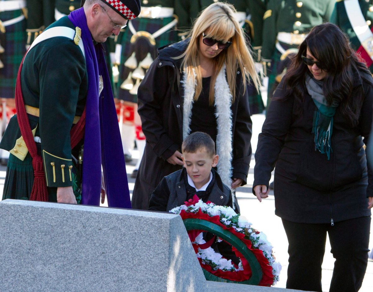 Cpl. Nathan Cirillo's sisters look on as Cirillo's son Marcus places a wreath at a memorial plaque on the one year anniversary of his death.