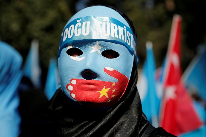 An ethnic Uighur demonstrator wears a mask as she attends a protest against China in front of the Chinese Consulate in Istanbul, Turkey, Oct. 1, 2019.