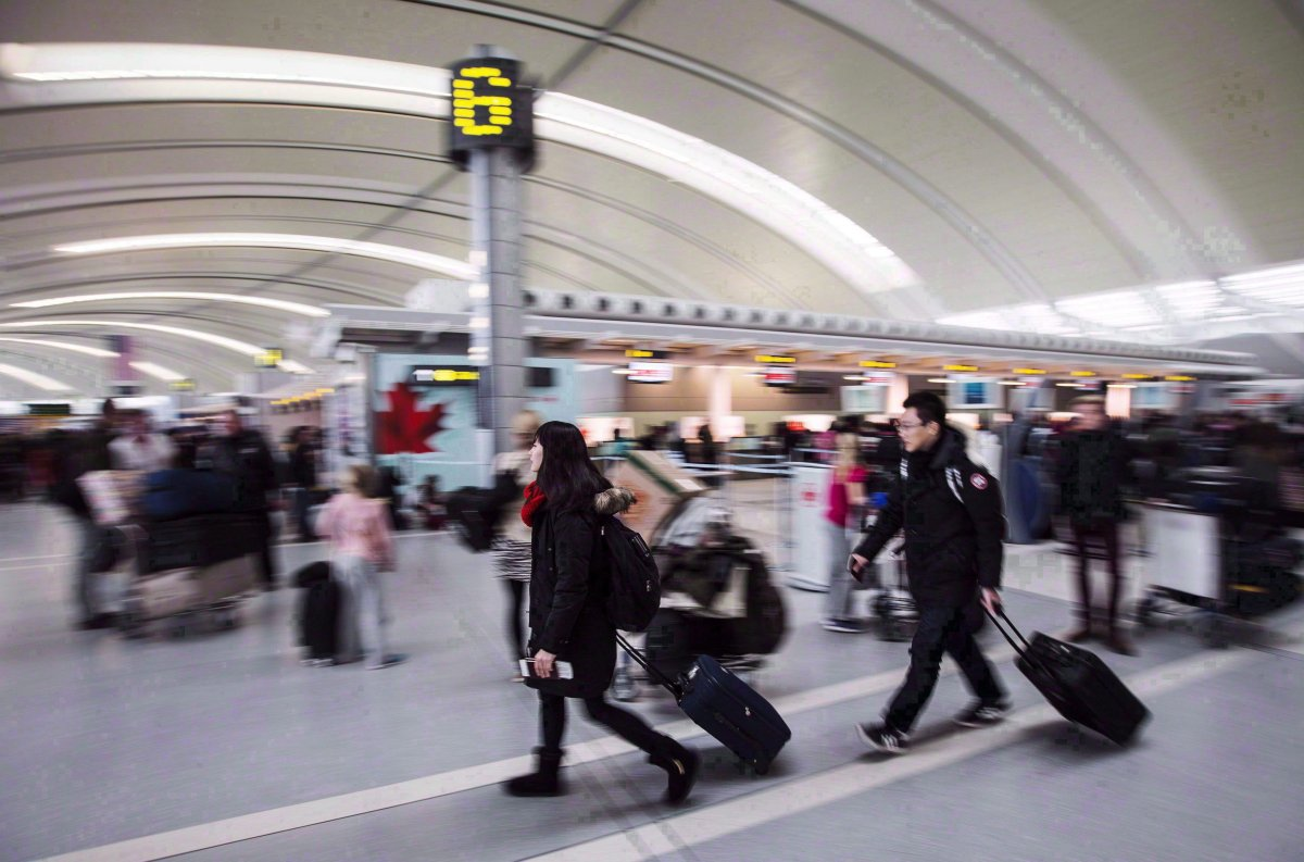 People carry luggage at Pearson International Airport in Toronto on Dec. 20, 2013.