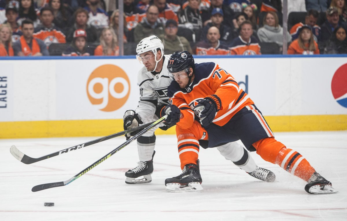 Los Angeles Kings' Sean Walker (26) and Edmonton Oilers' Oscar Klefbom (77) battle for the puck during first period NHL hockey action in Edmonton, Saturday, Oct. 5, 2019. THE CANADIAN PRESS/Jason Franson.