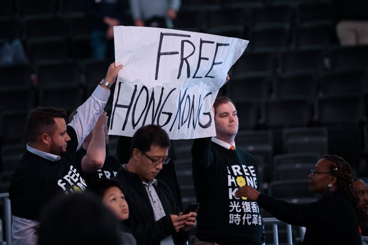 Activists hold up a sign before an NBA exhibition basketball game between the Washington Wizards and the Guangzhou Loong-Lions, Wednesday, Oct. 9, 2019, in Washington.