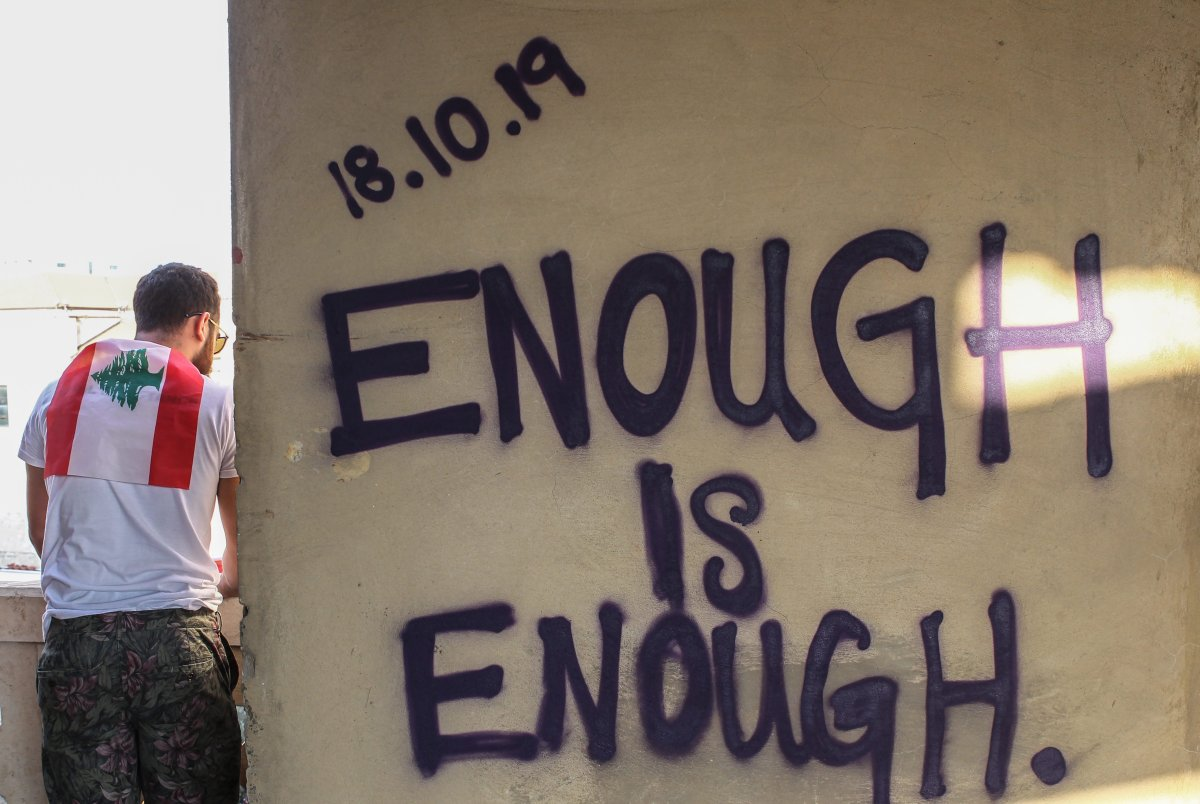 A man stands next to graffiti that spells out '18.10.2019 Enough is Enough' during a protest in downtown Beirut, Lebanon, 19 October 2019.