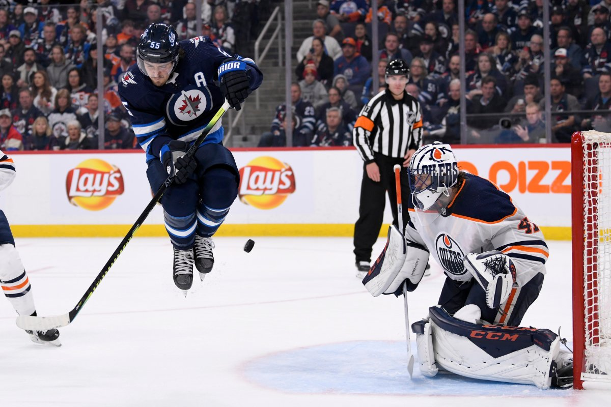 Winnipeg Jets' Mark Scheifele (55) jumps as puck is shot towards Edmonton Oilers' Mike Smith (41) during second period NHL action in Winnipeg on Sunday, Oct. 20, 2019. THE CANADIAN PRESS/Fred Greenslade.