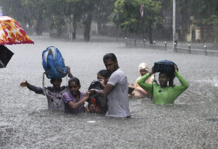 In this Sept. 4, 2019, file photo, people hold hands and navigate their way through a flooded street as it rains in Mumbai, India.