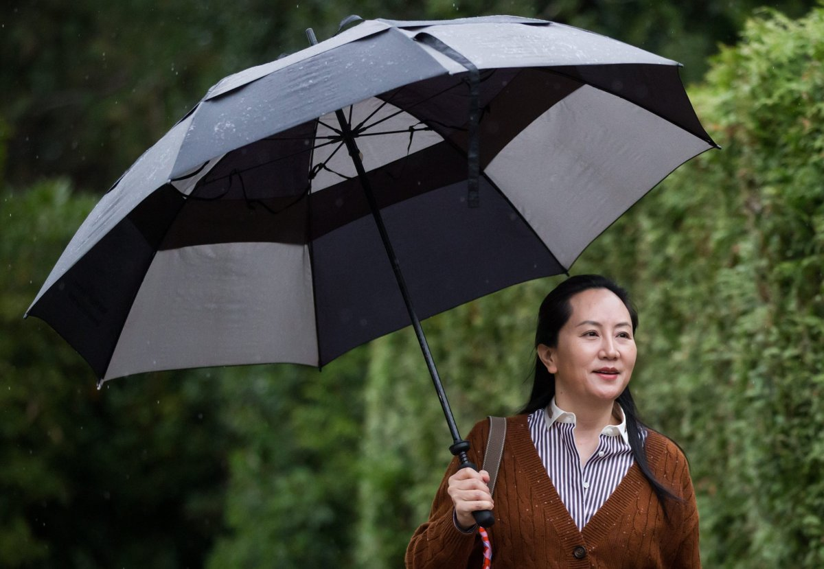Huawei chief financial officer Meng Wanzhou, who is out on bail and remains under partial house arrest after she was detained last year at the behest of American authorities, carries an umbrella to shield herself from rain as she leaves her home to attend a court hearing, in Vancouver, on Thursday October 3, 2019.