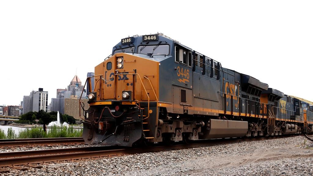FILE - In this June 24, 2019, file photo, a CSX freight train rolls past downtown Pittsburgh. The biggest U.S. freight railroads appear ready to renew their push to reduce their crews to one-person from the current two-man operation used at major railroads now. Eight U.S. railroads have filed a federal lawsuit against the union that represents rail conductors to force the SMART union to negotiate about crew sizes during the next round of contract talks that starts in November. (AP Photo/Gene J. Puskar, File).