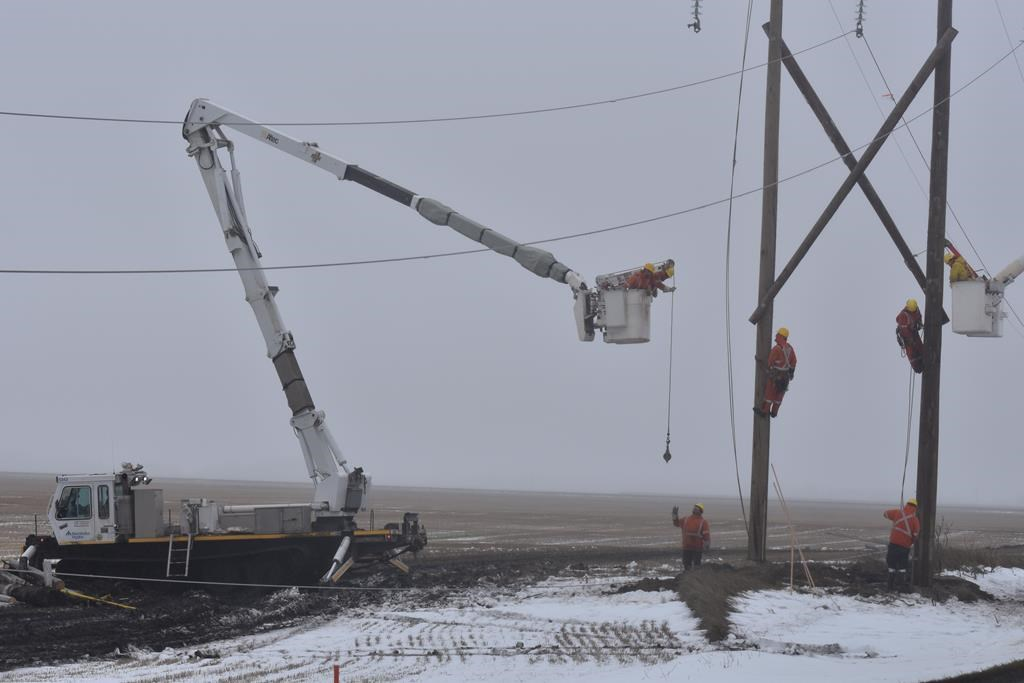Workers use a tracked vehicle to repair a damaged hydro pole in Portage La Prairie, Man., in a Tuesday, Oct. 15, 2019.