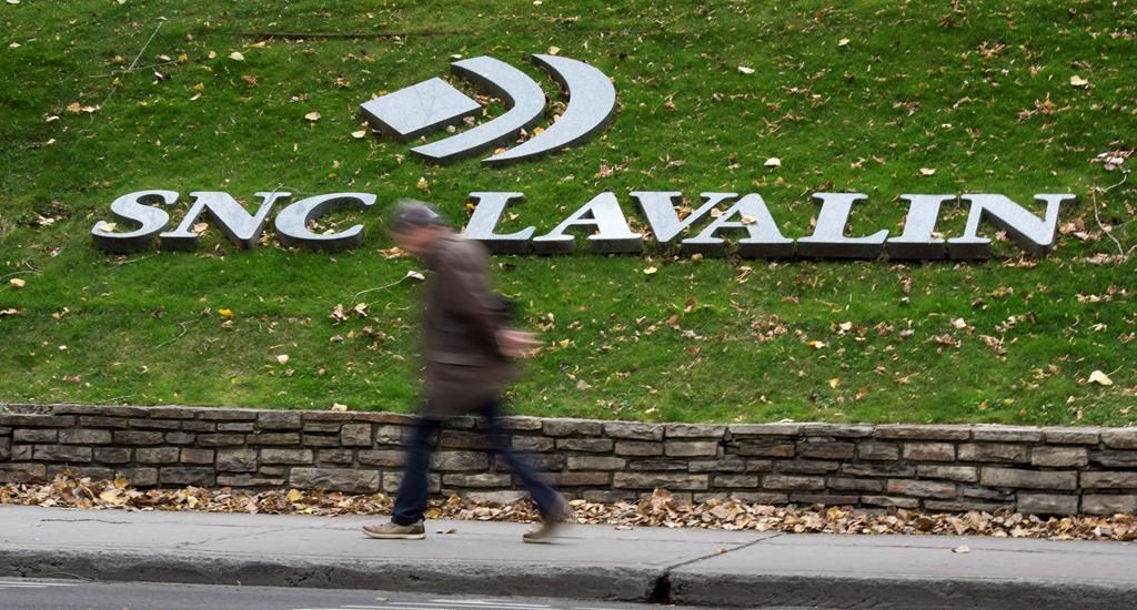 A man walks past the headquarters of SNC Lavalin Thursday, November 6, 2014 in Montreal.