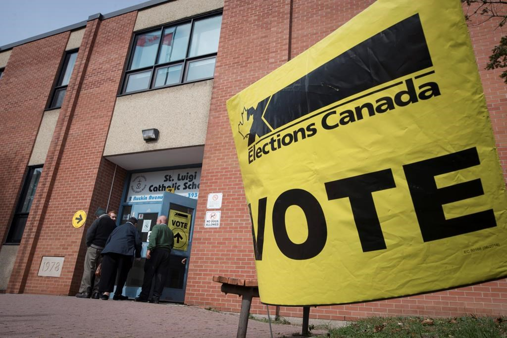 Voters enter the polling station at St. Luigi Catholic School during election day in Toronto on Monday, October 21, 2019.