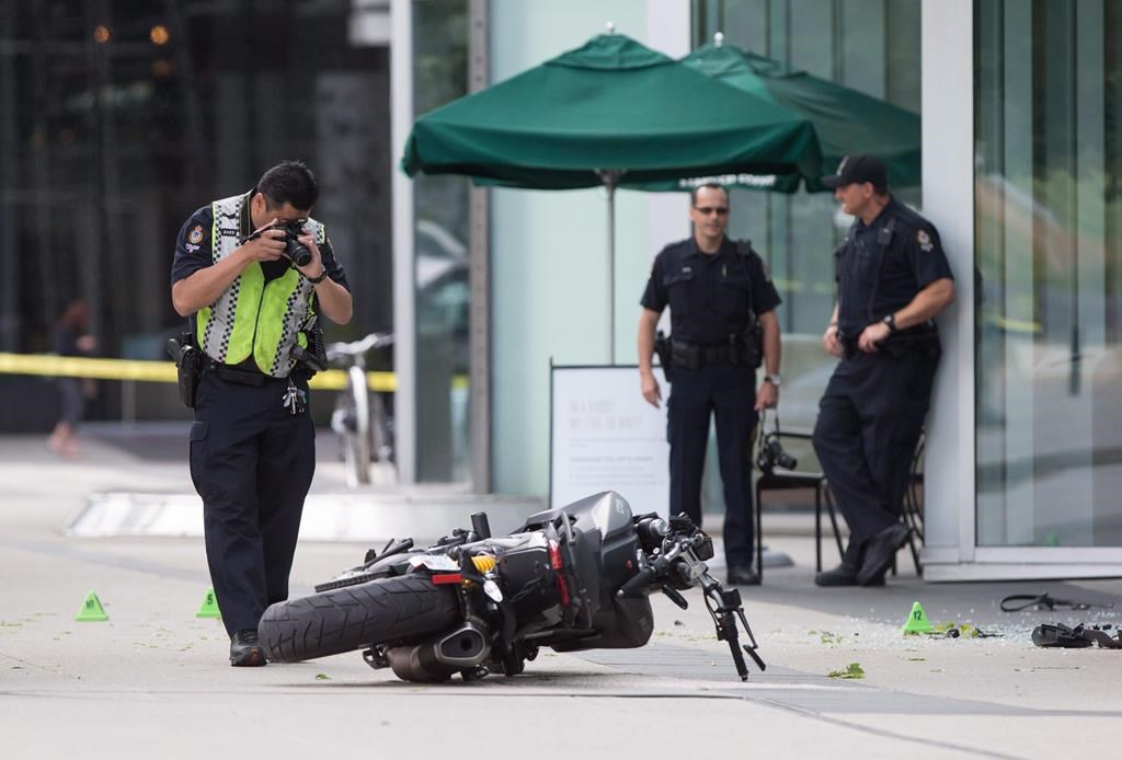 """A police officer photographs a motorcycle after a female stunt driver working on the movie """"Deadpool 2"""" died after a crash on set, in Vancouver, B.C., on Monday August 14, 2017. British Columbia's workplace safety agency says multiple failures of a production company contributed to the death of a stunt performer on the set of """"Deadpool 2.""""."""