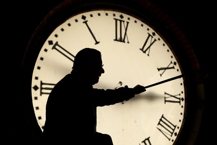 A man adjusts a courthouse clock for daylight saving time in this file photo.