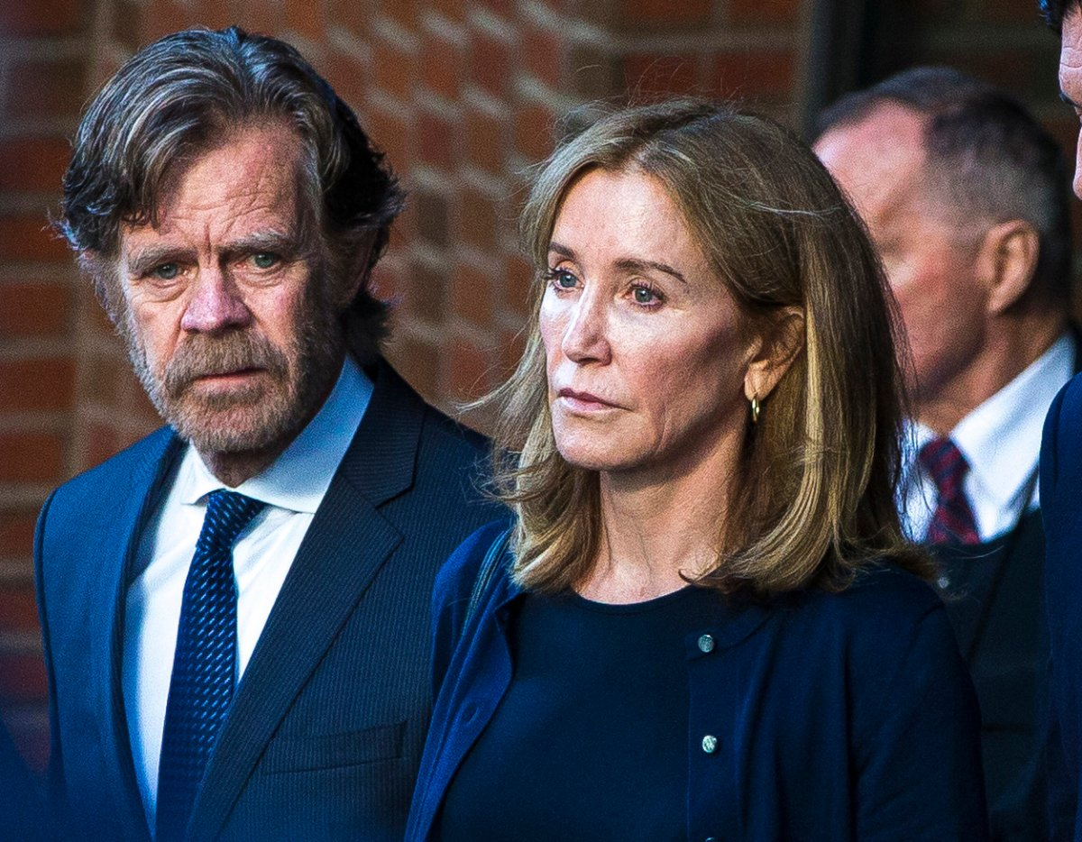 Felicity Huffman, right, and her husband, William H. Macy, walk out of the John Joseph Moakley United States Courthouse in Boston on Sep. 13, 2019.