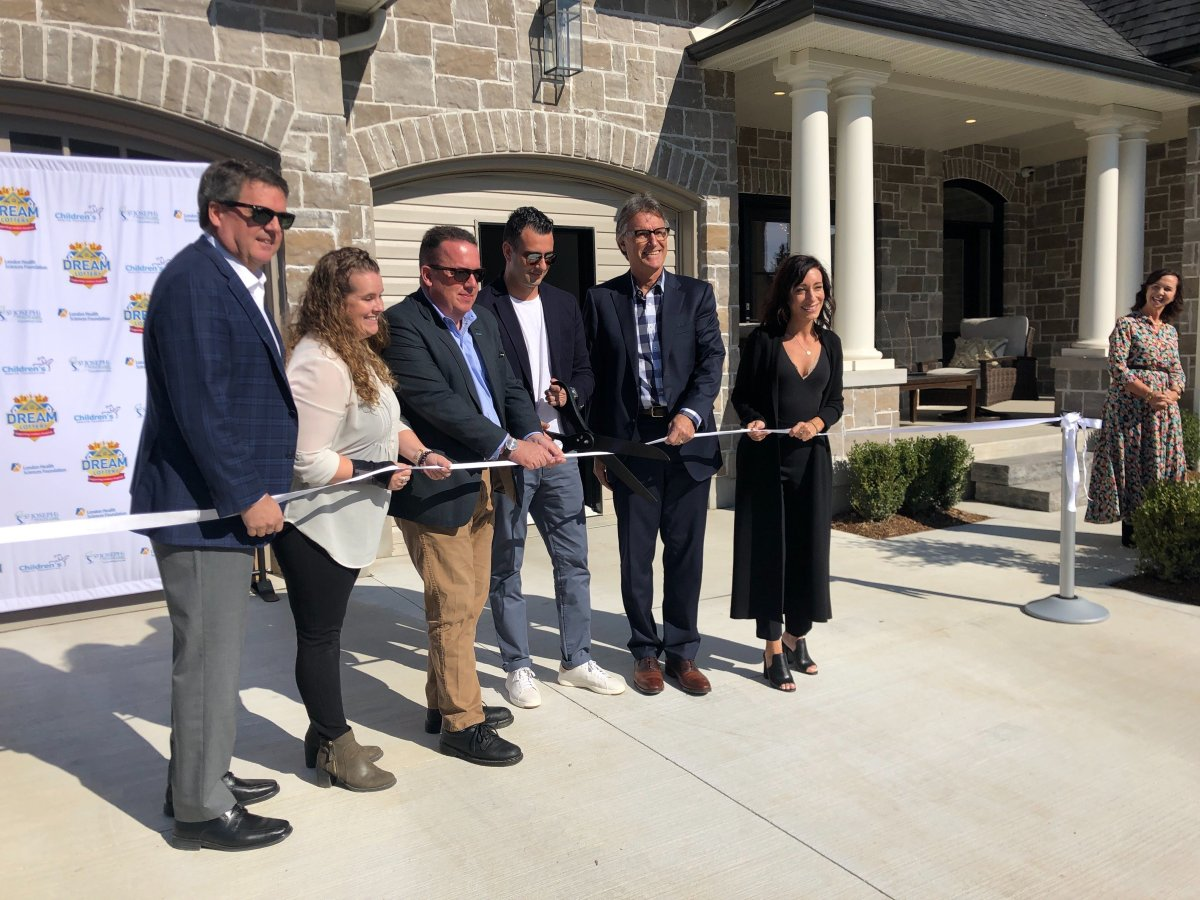 Officials cut the ribbon at the Highland Green Estates Dream Home at 54 Edwin Drive in London on Oct. 10, 2019.