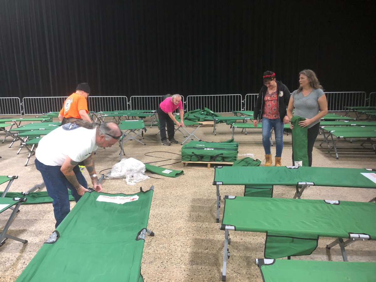 Volunteers prepare cots at the RBC Convention Centre, the site of a warming shelter for First Nations communities without power.