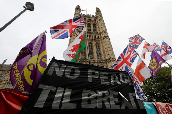 Various flags and banners fly in front of Parliament in London, Friday, Oct. 25, 2019. Politicians in Britain and the European Union seem to be looking to each other to break the Brexit deadlock.