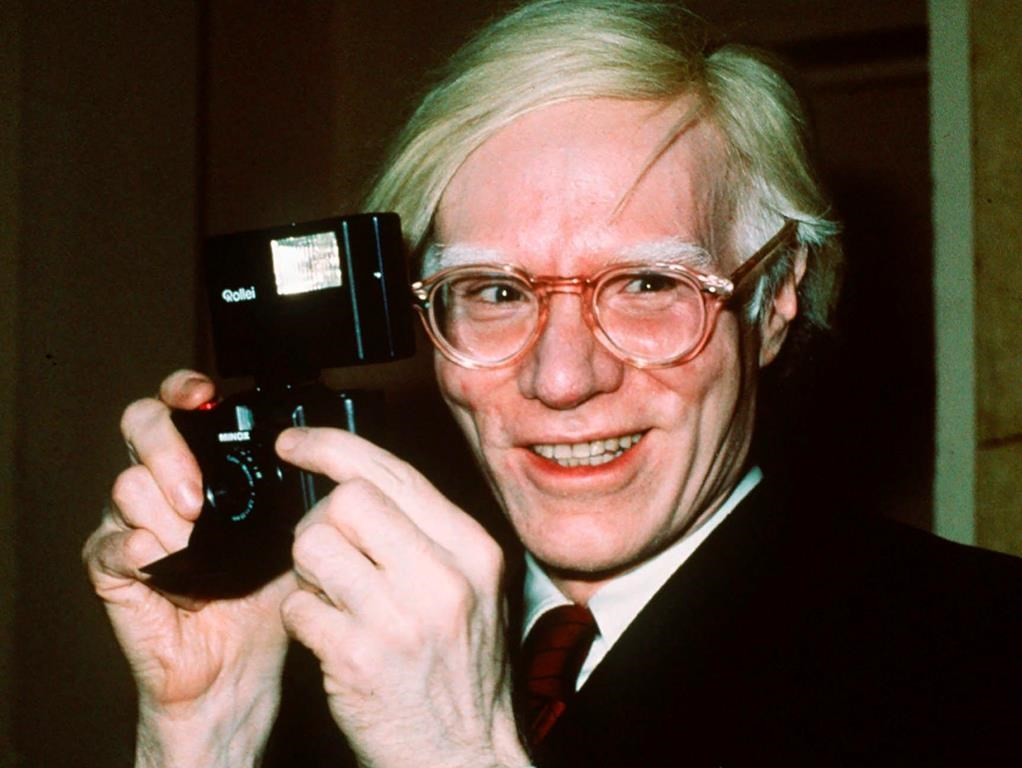 "FILE - In this file photo dated 1976, showing pop artist Andy Warhol smiles in New York. Andy Warhol's portraits of New York drag queens and trans women are going on display at London's Tate Modern art gallery, in ""a more human and personal look"", that aims to find new angles on the iconic American artist, in a show starting in March 2020."