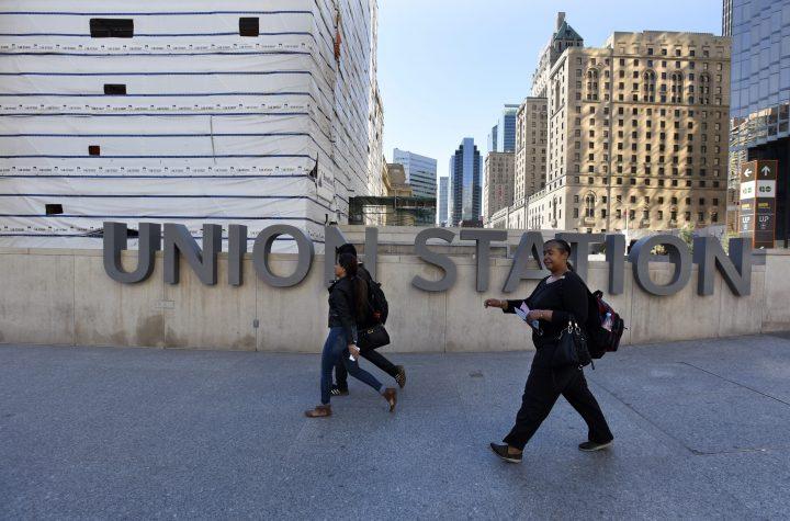 Pedestrians walk past a sign outside Toronto's Union Station.