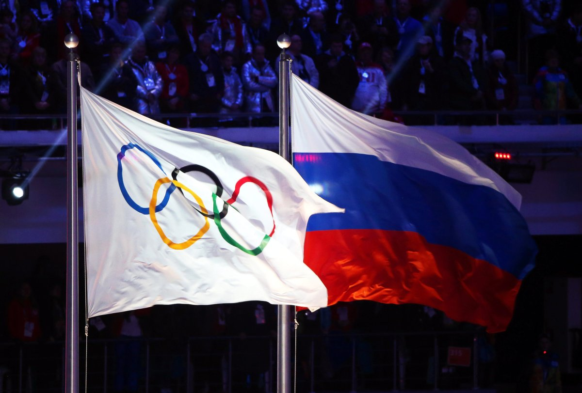 The Olympic flag (L) and the Russian flag (R) fly during the closing ceremony of the Sochi 2014 Olympic Games at Fisht Olympic Stadium in Sochi, Russia, in 2014.