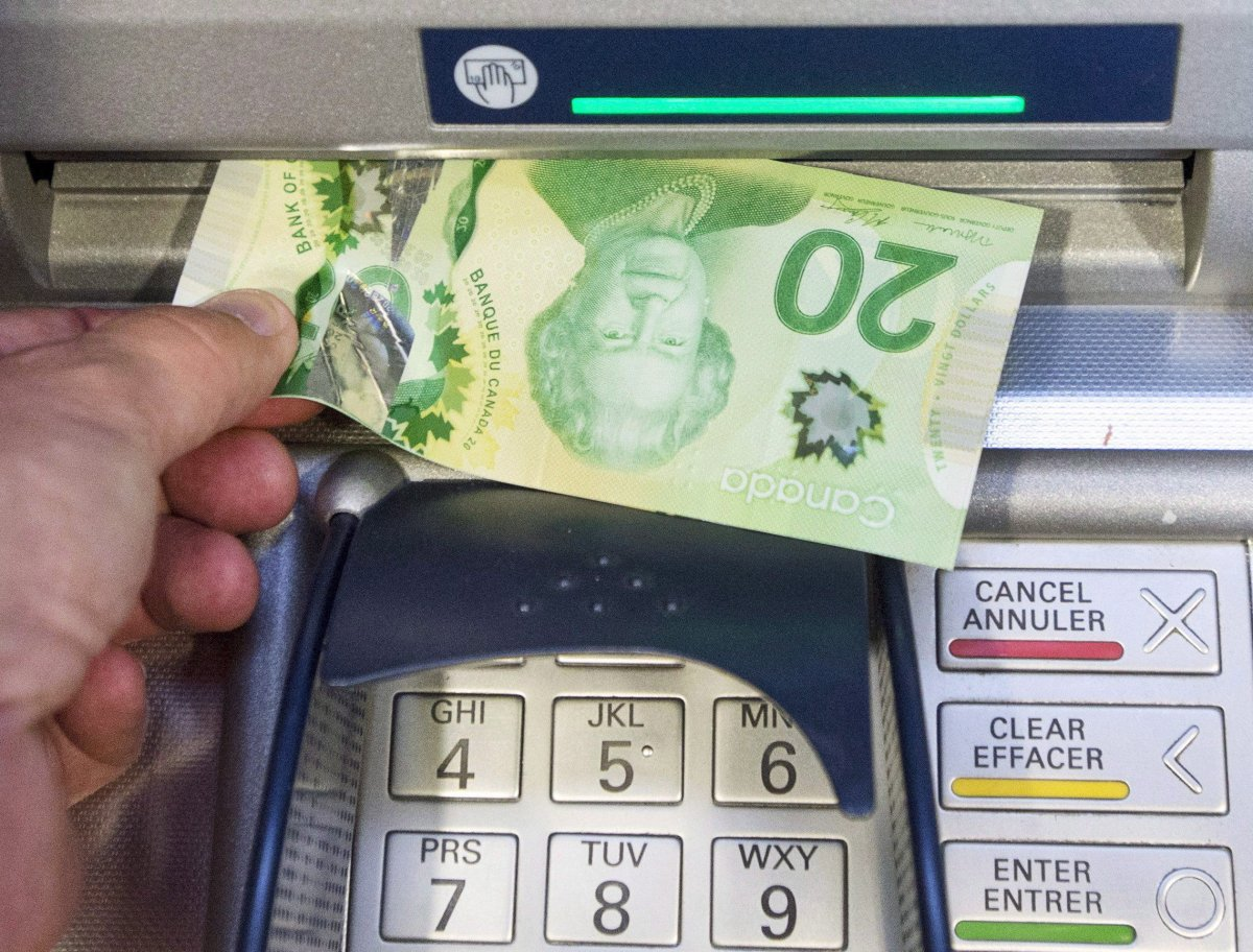 Money is removed from a bank machine on Monday, May 30, 2016 in Montreal.