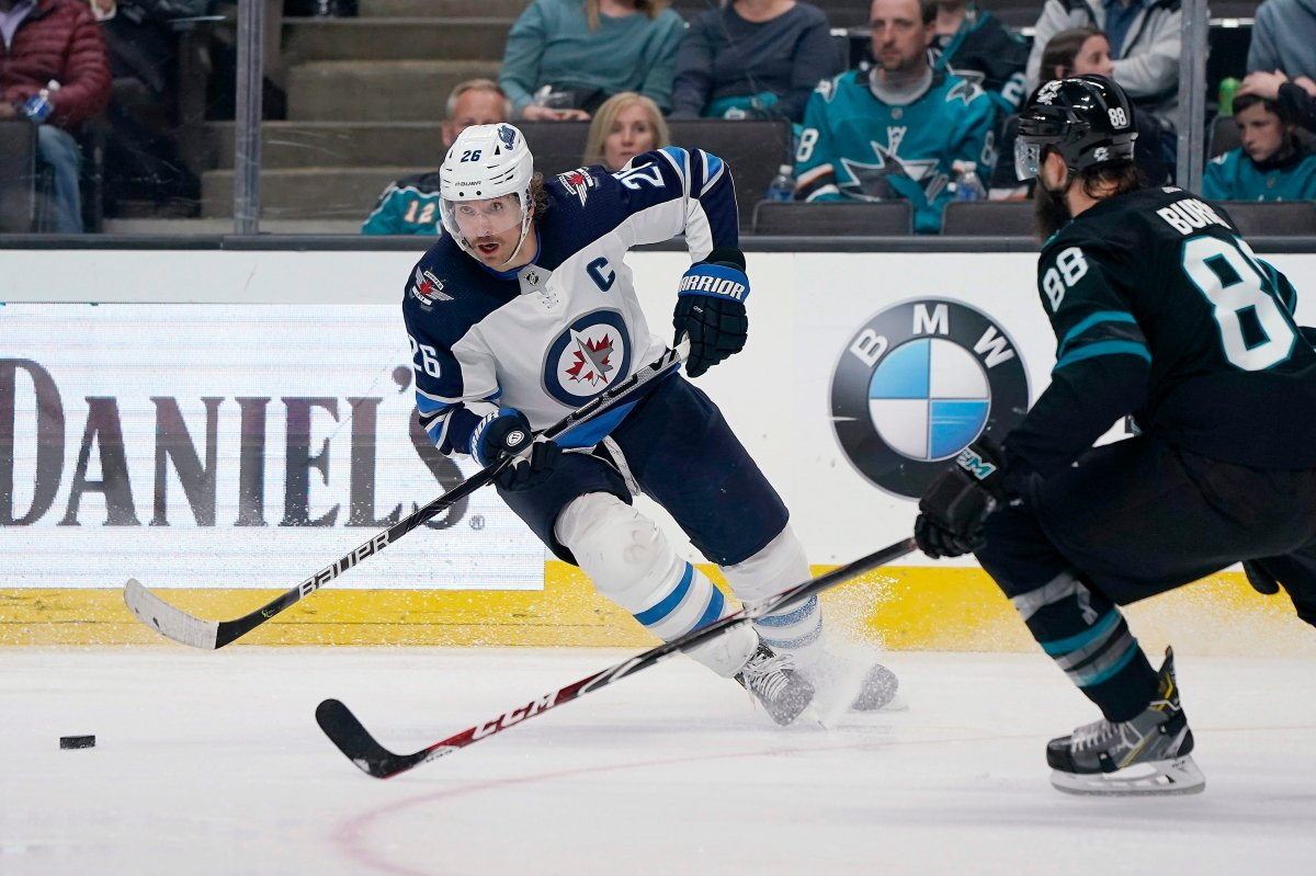 Winnipeg Jets right wing Blake Wheeler (26) moves the puck next to San Jose Sharks defenceman Brent Burns (88) during the second period of an NHL hockey game in San Jose, Calif., Friday, Nov. 1, 2019.