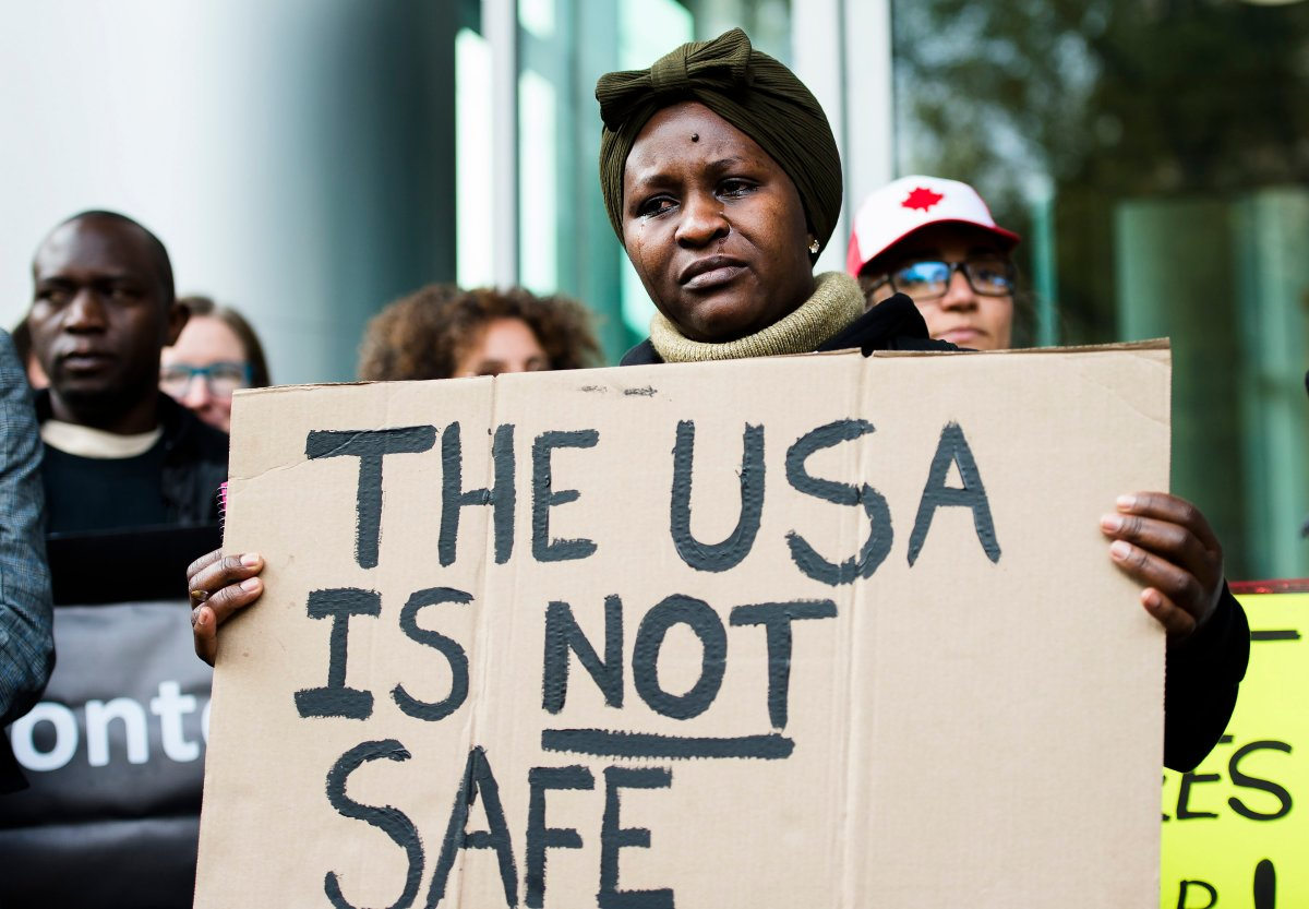 Kikome Afisa cries as she along with others protest outside the Federal Court of Canada building for a hearing of the designation of the U.S. as a safe third country for refugees in Toronto on Monday, November 4, 2019.