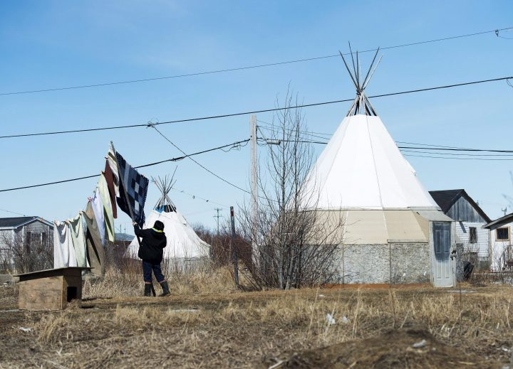 An indigenous women takes down laundry in the northern Ontario First Nations reserve in Attawapiskat, Ont., on April 19, 2016.