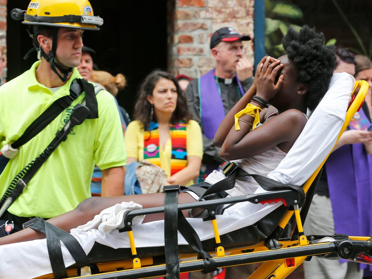 FILE - In this Aug. 12, 2017, file photo, an emergency employee helps an injured person after a neo-Nazi drove his car into a group of counter-protesters at a white nationalist rally in Charlottesville, Va.