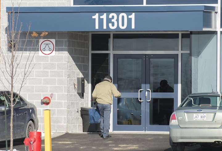 A man enters a building in an industrial park in Montreal, Thursday, November 21, 2019, where it is believed that children attend a school run by a religious group.
