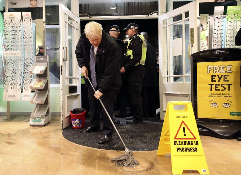 Britain's Prime Minister Boris Johnson visits an optician shop after flooding, in Matlock, north England, Friday Nov. 8, 2019. A woman died after being swept away by surging waters as torrential rain drenched parts of north and central England, swelling rivers, forcing evacuations and disrupting travel for a second day Friday.