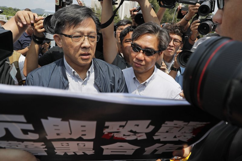 In this Aug. 12, 2019, photo, pro-Beijing lawmaker Junius Ho, left, attends a demonstration of an anti-riot vehicle equipped with water cannon at the Police Tactical Unit Headquarters in Hong Kong. Hong Kong police say an anti-government supporter stabbed and wounded the pro-Beijing lawmaker who was campaigning for local elections. The government condemned the attack on Wednesday, Nov. 6, 2019 against Ho, a hate figure for protesters, and said police arrested the assailant.