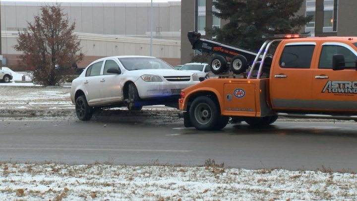 A tow truck removes a car from a median on Airport Drive in Saskatoon on Friday, Nov. 8, 2019. Police said icy roads may be a factor in multiple collisions in and around Saskatoon.