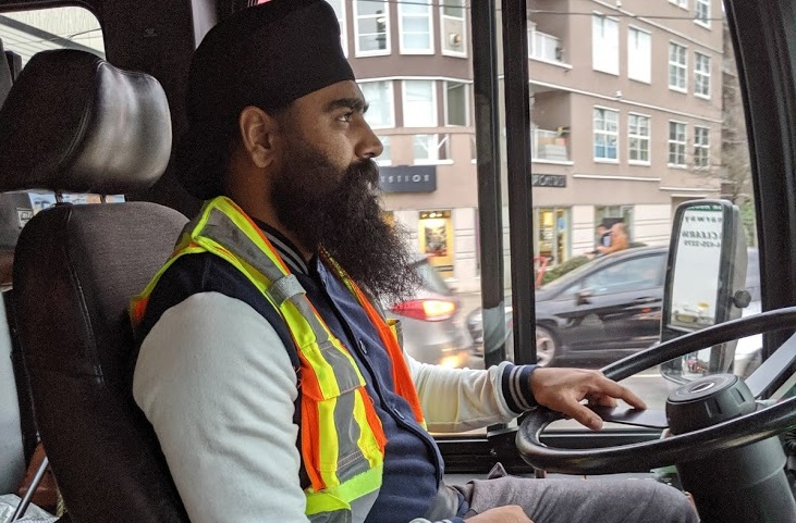 A Metro Vancouver bus driver works out of uniform as a part of ongoing job action.